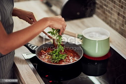 Mixed race woman in apron standing next to stove, stirring tomato sauce and adding rocket. On stove is pot with boiling pasta.