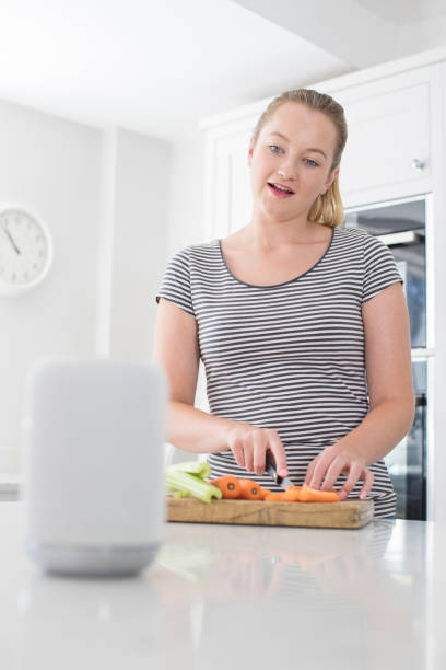 Woman Preparing Food At Home Asking Digital Assistant Question Woman Preparing Food At Home Asking Digital Assistant Question smart speaker stock pictures, royalty-free photos & images