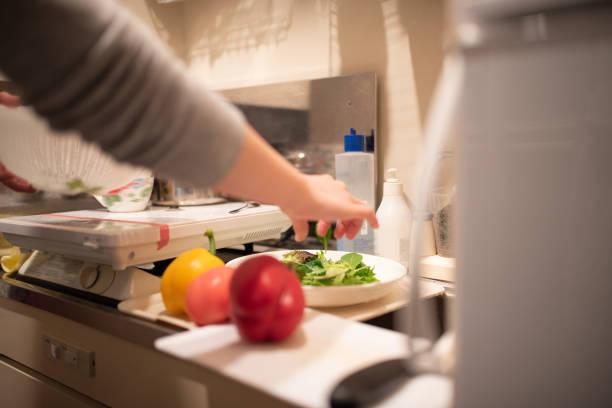 キッチンで朝食の準備をする女性: 手のクローズアップ - 独身の若者 ストックフォトと画像