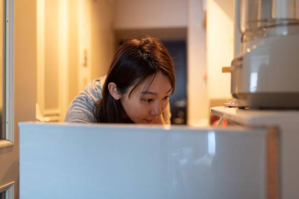 キッチンで朝食の準備をする女性 - 独身の若者 ストックフォトと画像