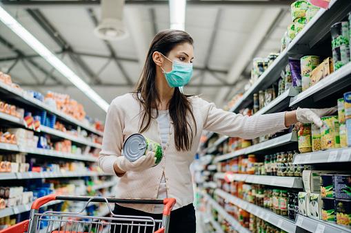 Woman preparing for pathogen virus pandemic spread quarantine.Choosing nonperishable food essentials.Budget buying at a supply store.Pandemic quarantine preparation.Emergency to buy list