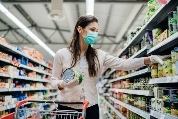 Woman preparing for pathogen virus pandemic spread quarantine.Choosing nonperishable food essentials.Budget buying at a supply store.Pandemic quarantine preparation.Emergency to buy list Woman preparing for pathogen virus pandemic spread quarantine.Choosing nonperishable food essentials.Budget buying at a supply store.Pandemic quarantine preparation.Emergency to buy list buying stock pictures, royalty-free photos & images