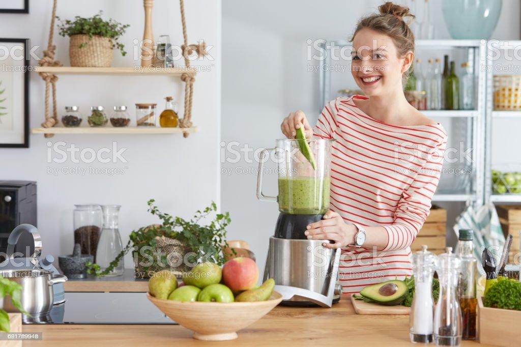 Woman preparing green smothie stock photo