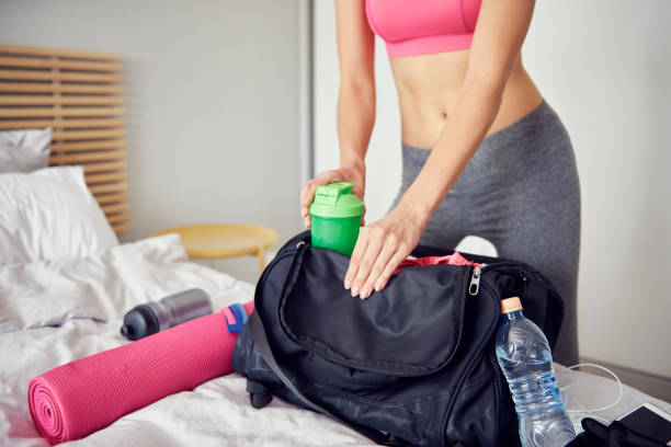 Woman preparing gym bag for all day stock photo