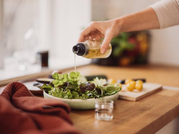 Frau bereitet gesunden Salat in der Küche zu – Foto