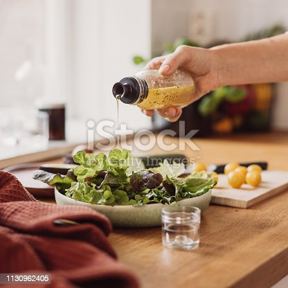 Woman preparing healthy salad in kitchen. Close up of woman preparing food adn vegetables. Pouring vinegar salad dressing. Bright photo taken in sunlight with stobes.