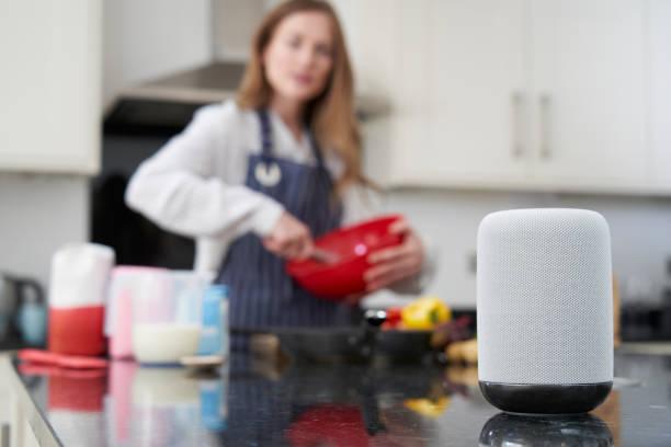 Mulher que prepara a refeição em casa que pede a pergunta do assistente digital - foto de acervo