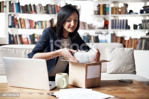 istock Woman preparing parcel for shipment 457207679