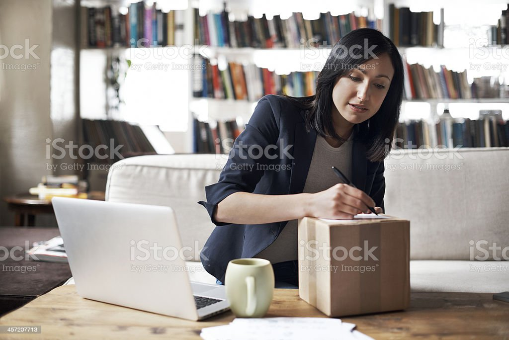 Woman preparing parcel for shipment stock photo