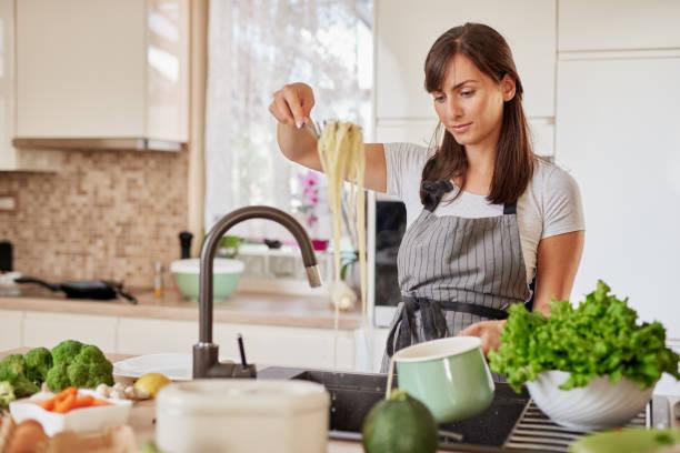 Frau bereitet Spaghetti. – Foto
