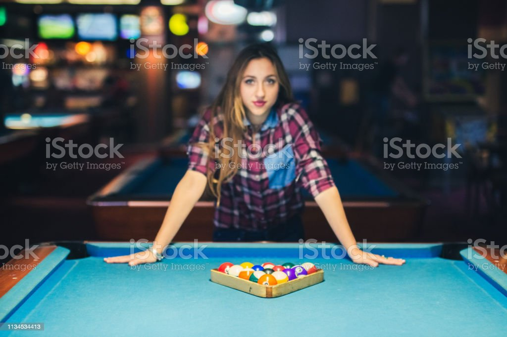 Young caucasian woman preparing table for billiard game.