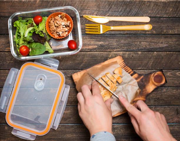 Frau zum Mitnehmen Zubereitung für ihr Kind. Schule-Lunch-Box mit Salat, gebratenes Huhn und Nüssen auf rustikalen hölzernen Hintergrund. Gesunde Ernährung Gewohnheiten Konzept. – Foto