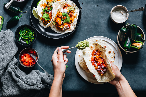 Point of view shot of a woman preparing tasty vegan tacos in kitchen. Female hands put fillings in tacos.