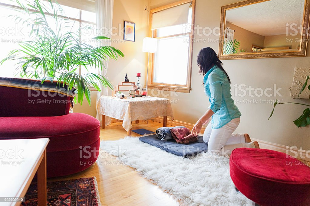 Woman preparing to meditate at home stock photo