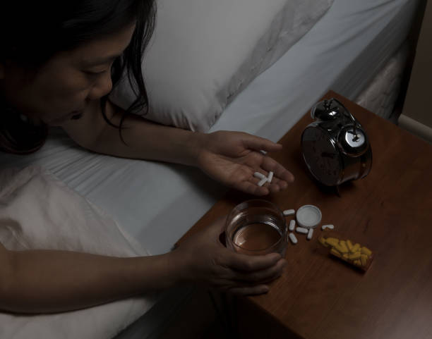 woman preparing to take pain killer pains at nighttime - sleeping pill stock photos and pictures