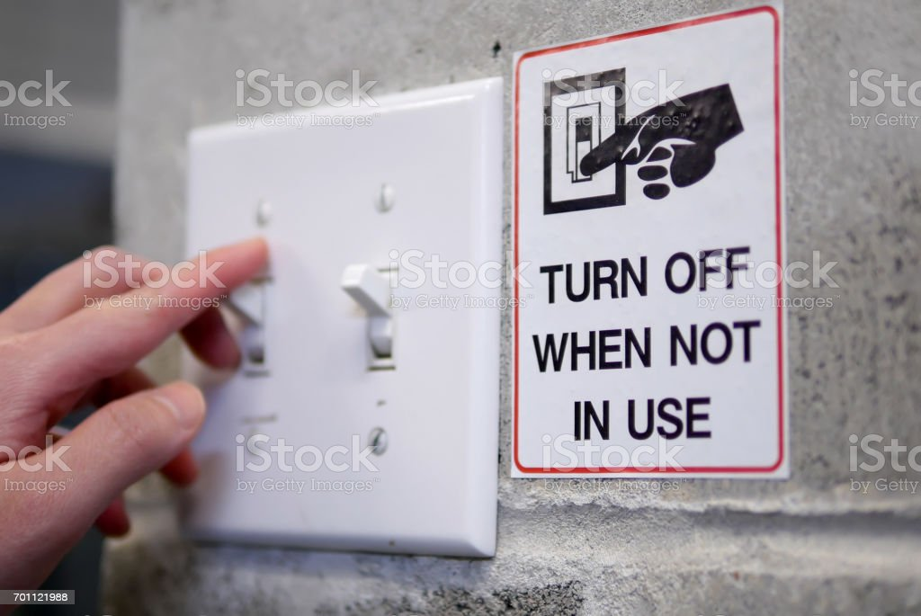 Woman preparing to turn off light switch by saving power concept stock photo
