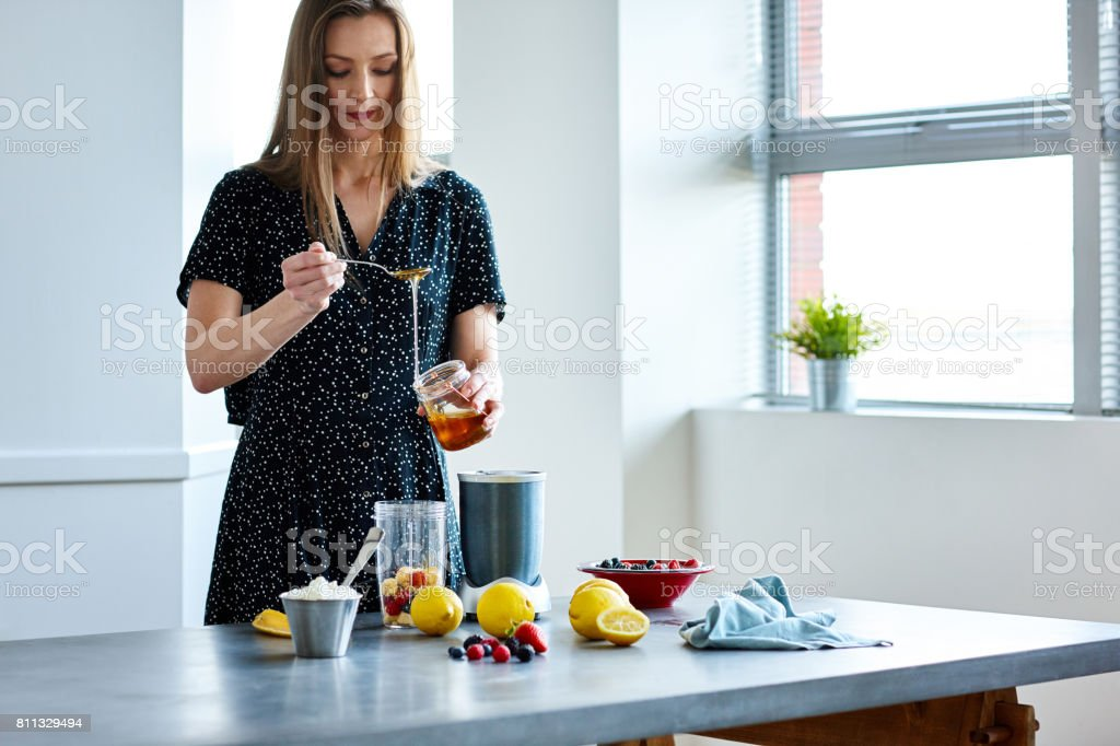 Woman preparing tropical beverage at home stock photo
