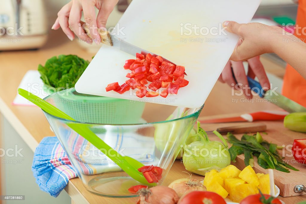 Woman preparing vegetables salad slicing red pepper stock photo