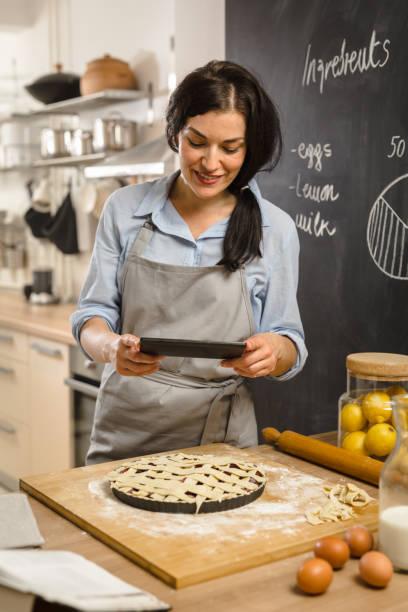 Tarte preparingsweet femme dans sa cuisine - Photo