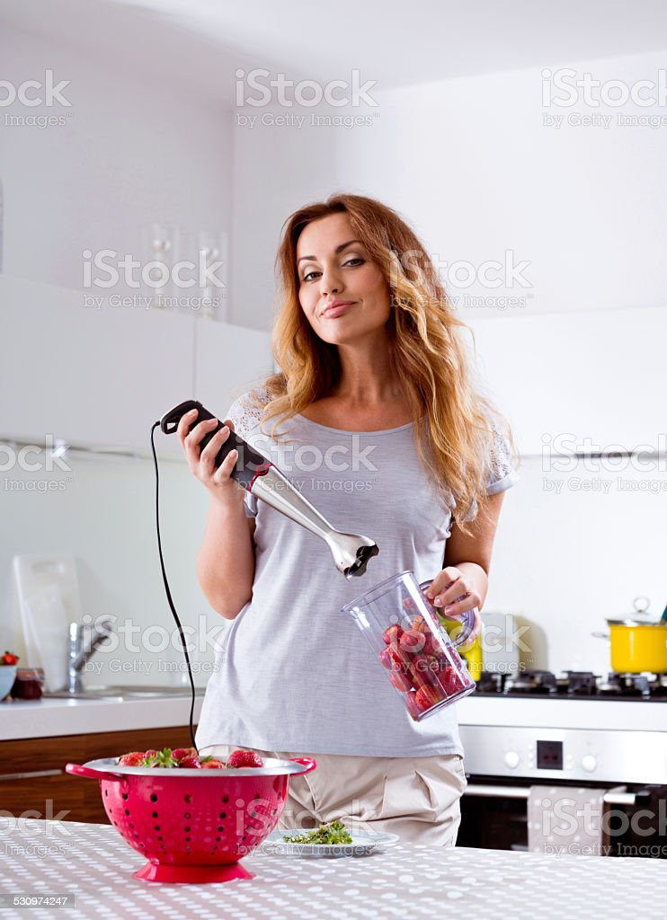 Woman prepering strawberry smoothie juice stock photo