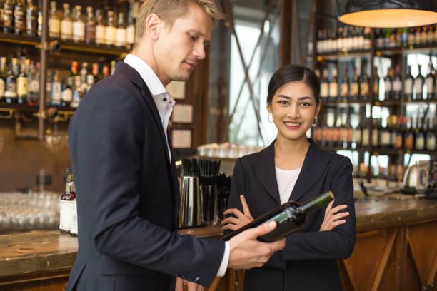 Frau anwesend Wein für Geschäftsmann in Bar mit attraktiven Lächeln auf den Lippen. Menschen mit Business-Konzept. – Foto