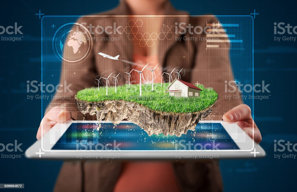 Woman presenting a perfect ecology land with a house and windmills stock photo