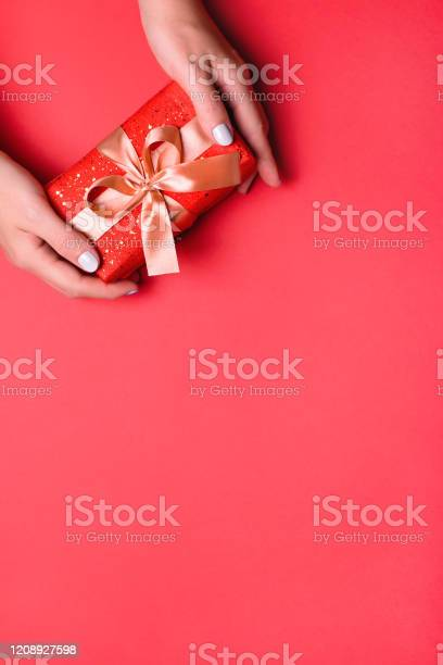 Woman presenting gift box top view on red background with golden picture id1208927598?b=1&k=6&m=1208927598&s=612x612&h=ftgeeuguswsgddnzsebrt0b9kdrojfoyxnzibmmzdcu=
