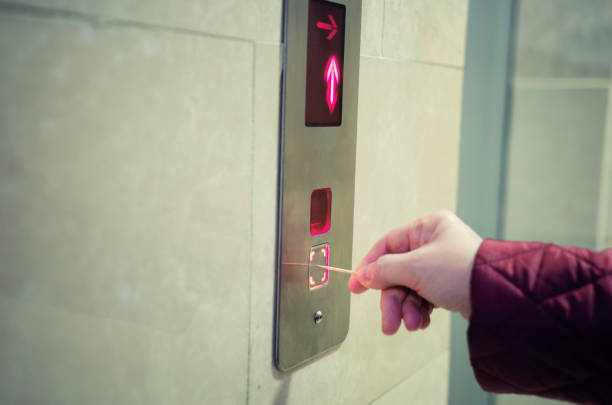 А woman presses the elevator button with a toothpick. stock photo