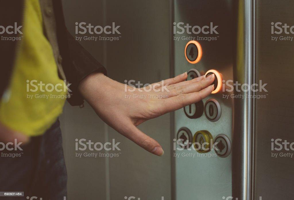 Presionar el botón mujer dentro del elevador. - foto de stock