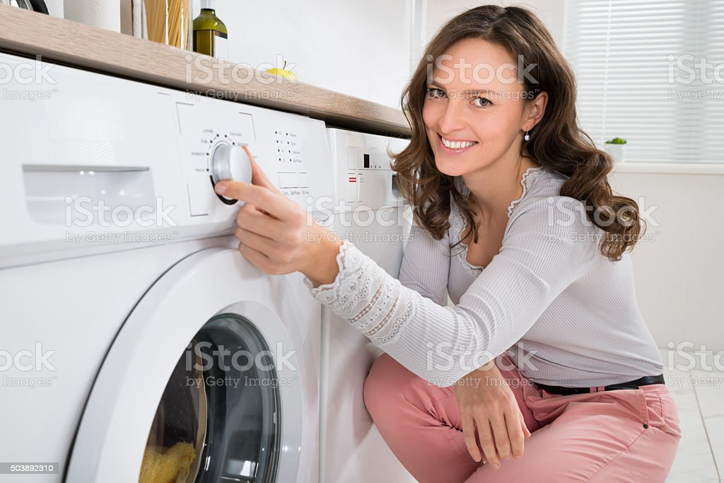 Woman Pressing Button Of Washing Machine stock photo