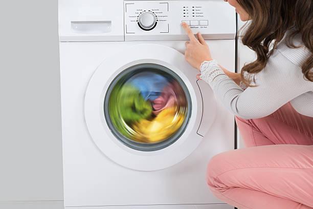 女性の洗濯機のボタンを押す - 衣類乾燥機 ストックフォトと画像