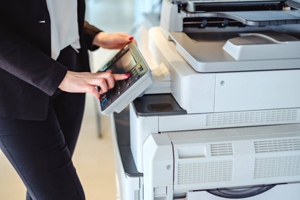 Woman pressing button on a copy machine in the office stock photo