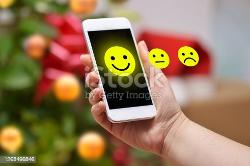 Woman pressing happy icon a smart phone with a Christmas tree background at home