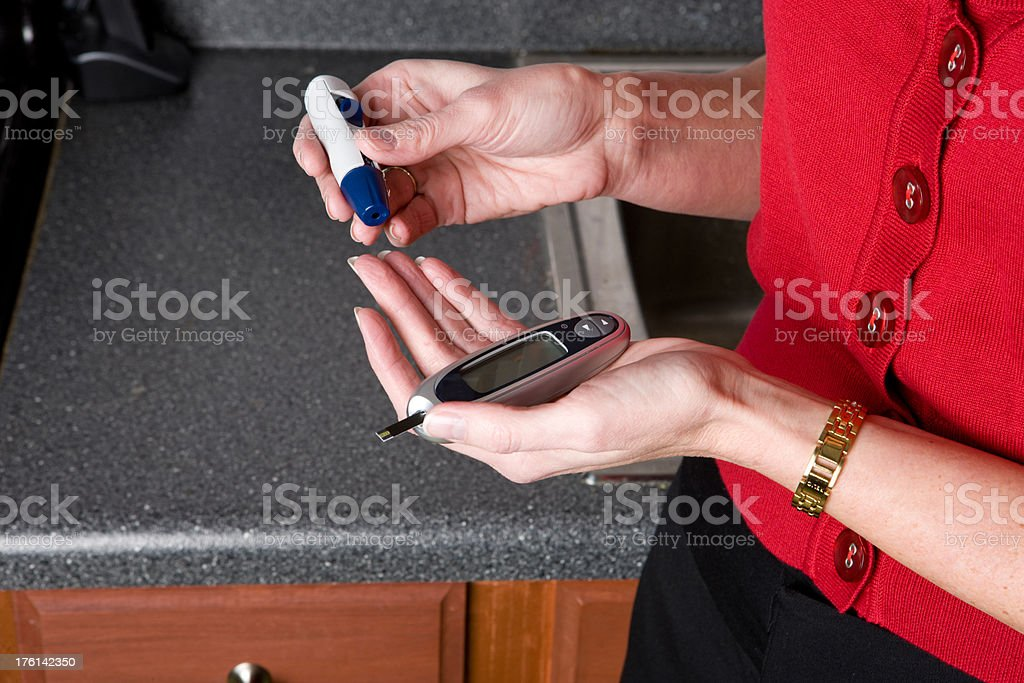 Woman Pricks Her Finger In Kitchen For Blood Test royalty-free stock photo