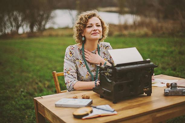 Mulher velha máquina de escrever sendo impressas impressões em vintage - foto de acervo