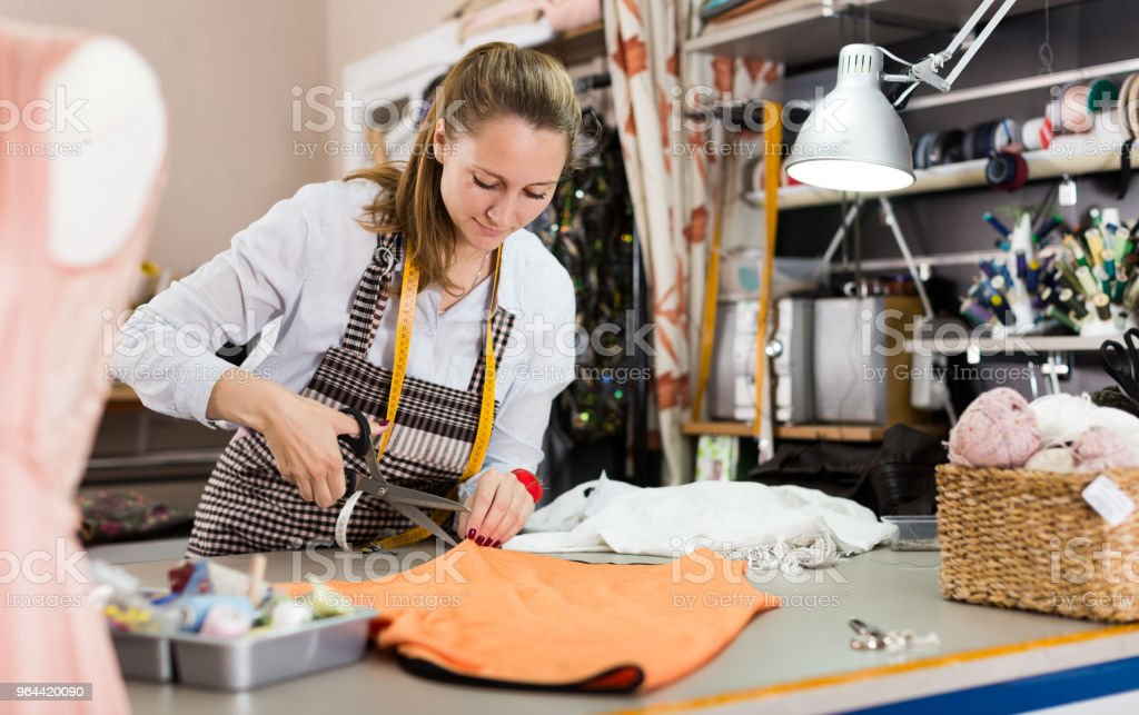 Woman professional working with material at sewing workshop - Royalty-free Caucasian Ethnicity Stock Photo