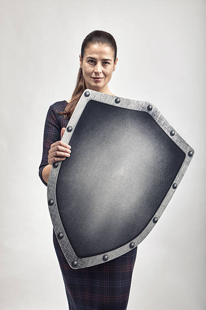 Woman protecting herself with a shield Woman protecting herself with a shield shielding stock pictures, royalty-free photos & images