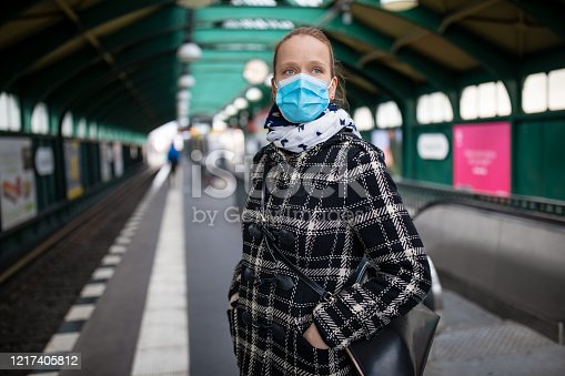 Woman in winter coat with protective mask on face standing on metro station. Female commuter waiting for the train during Covid-19 outbreak.