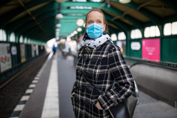 Woman protective face mask on metro station Woman in winter coat with protective mask on face standing on metro station. Female commuter waiting for the train during Covid-19 outbreak. subway platform stock pictures, royalty-free photos & images
