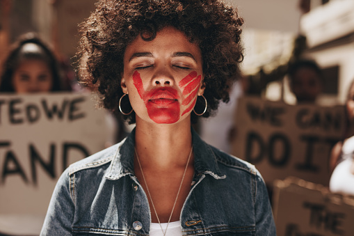 istock Woman protesting against domestic violence 1069158372