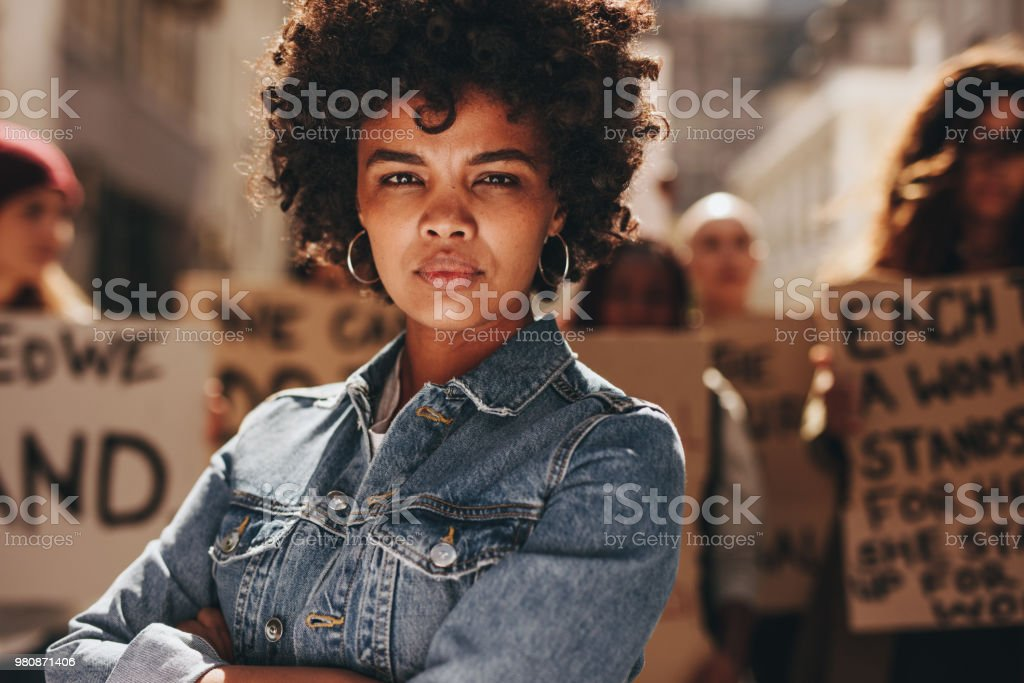 Woman protesting with group of activists stock photo
