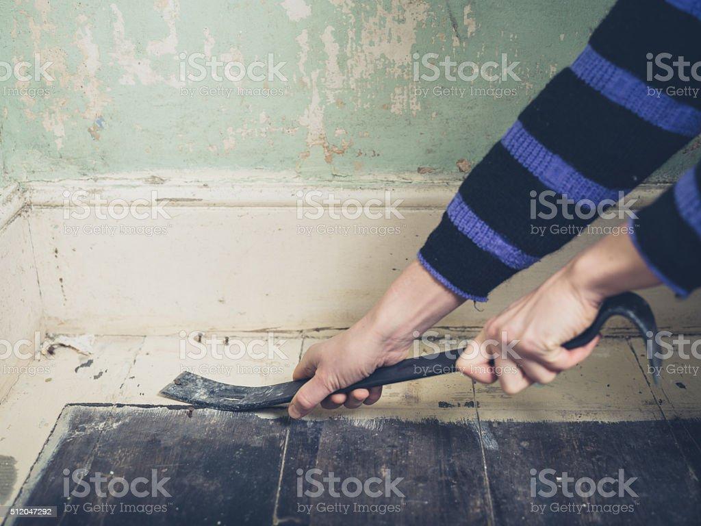 Woman prying nail with crowbar stock photo
