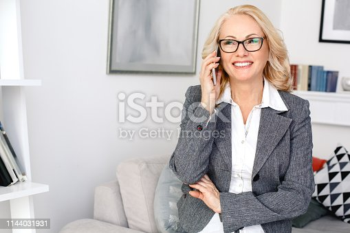 Middle-aged woman psychologist standing at casual home office wearing eyeglasses answering talking with client phone call smiling joyful