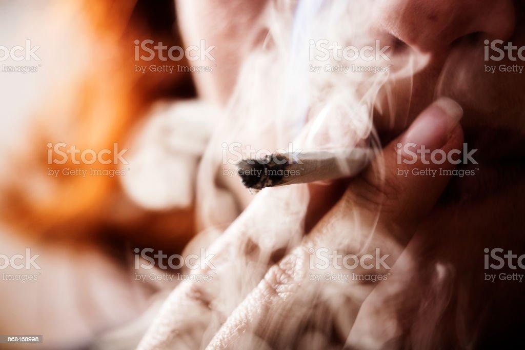 Woman puffs on a marijuana joint stock photo