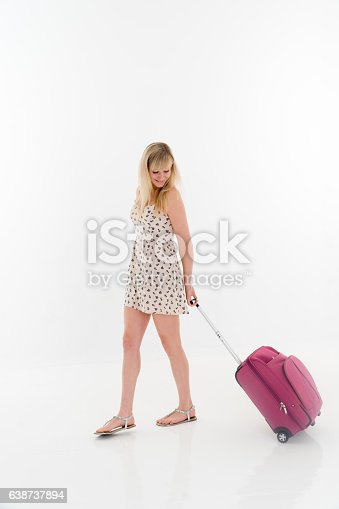 Young woman pulling a luggage white background.
