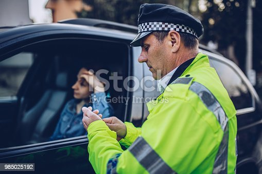 Young woman pulled over by police officer on the road.
