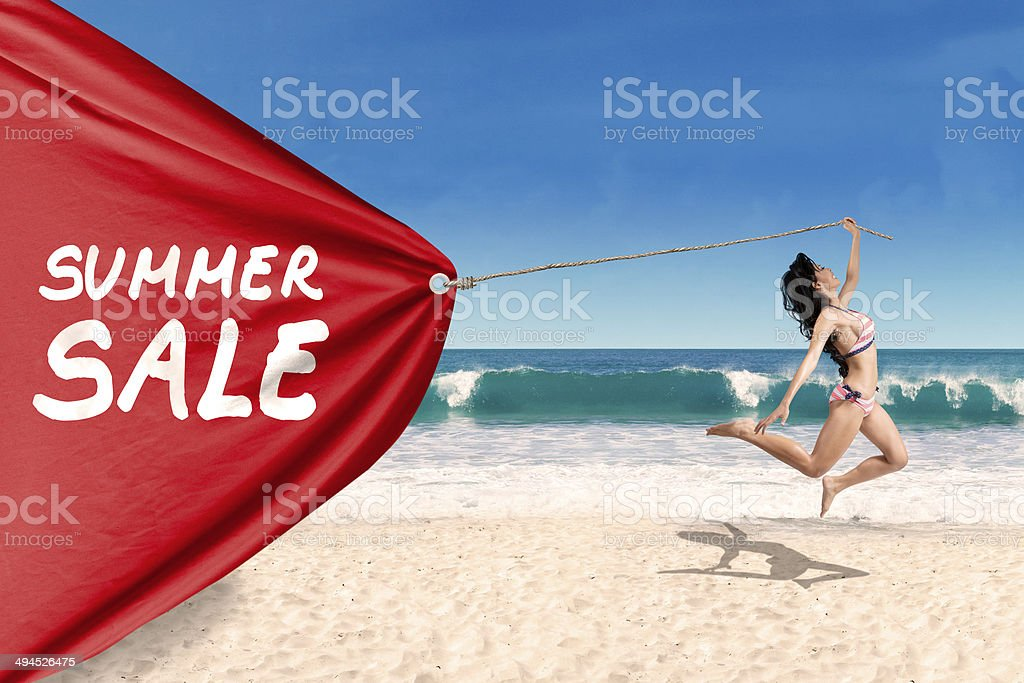 Woman pulling a banner of summer sale stock photo