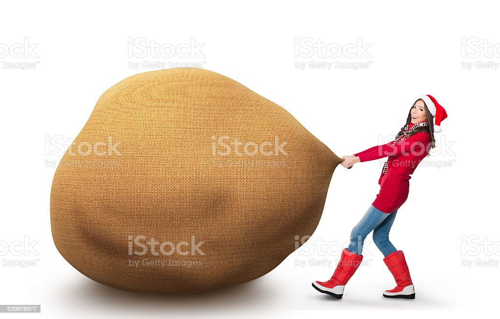 Woman pulling a big Santa's bag isolated on white stock photo