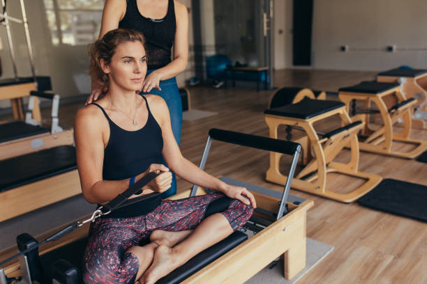 Woman pulling a stretch band  sitting on pilates training machine Fitness women sitting with legs crossed on a pilates training machine and pulling the stretch band. Pilates trainer guiding a woman at the gym doing strength training. jacoblund stock pictures, royalty-free photos & images