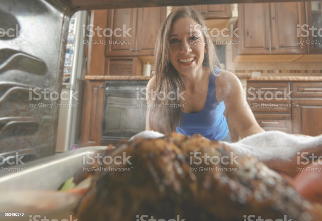 Woman pulling chicken out of oven stock photo